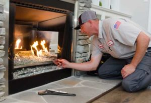 service tech fixing a fireplace